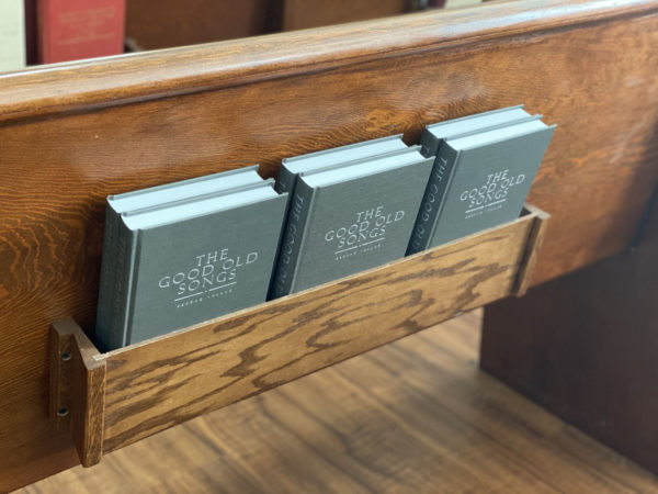 Six The Good Old Songs hymnals in the back of a pew